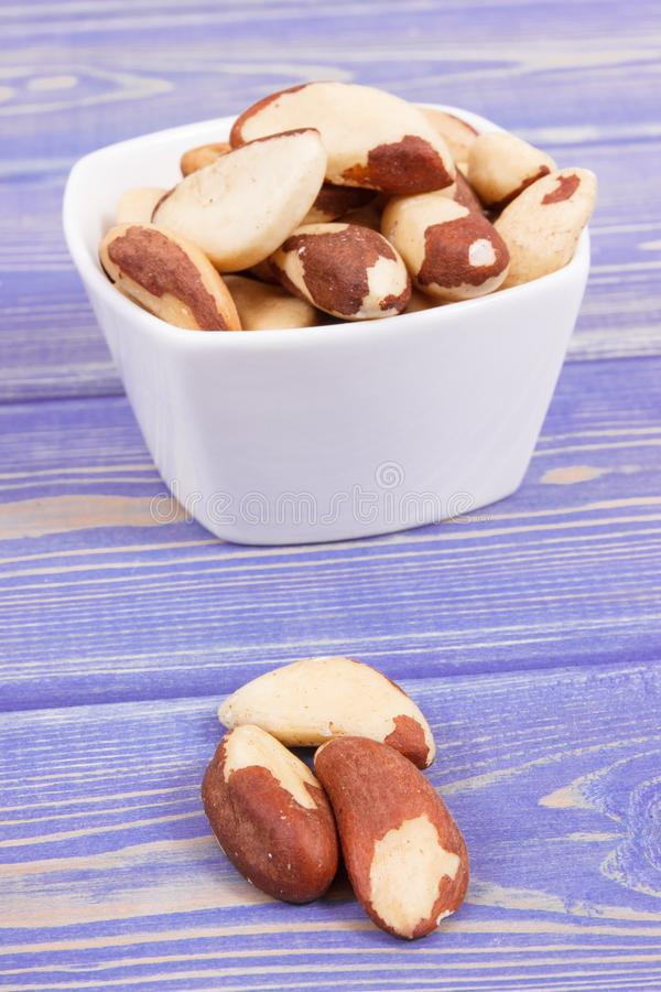 Heap of brazil nuts in bowl on old boards royalty free stock photo