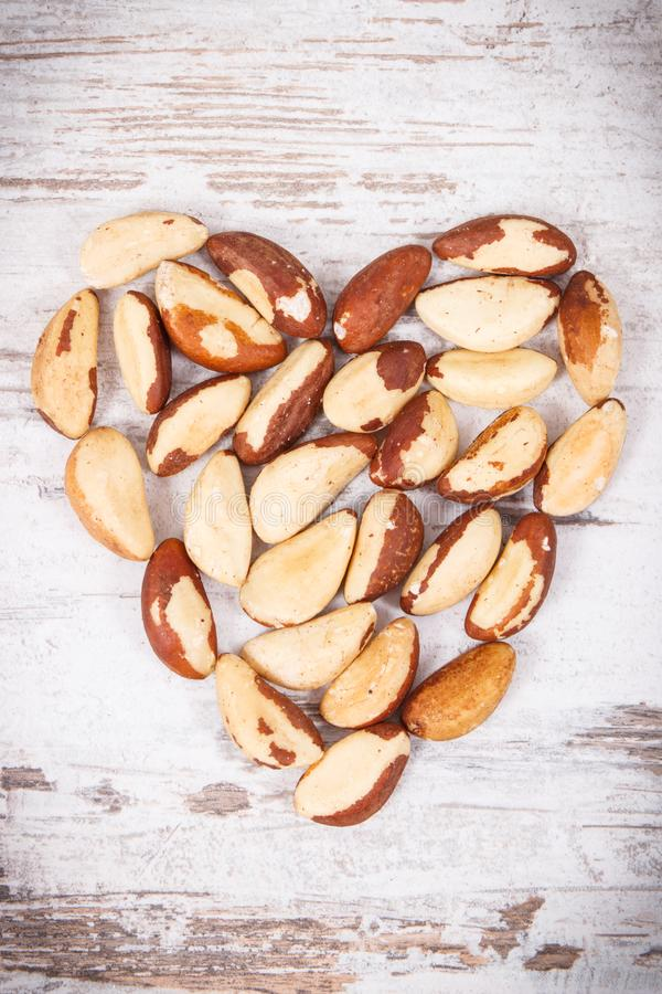 Heap of brazil nuts in shape of heart, healthy food containing natural minerals stock photos