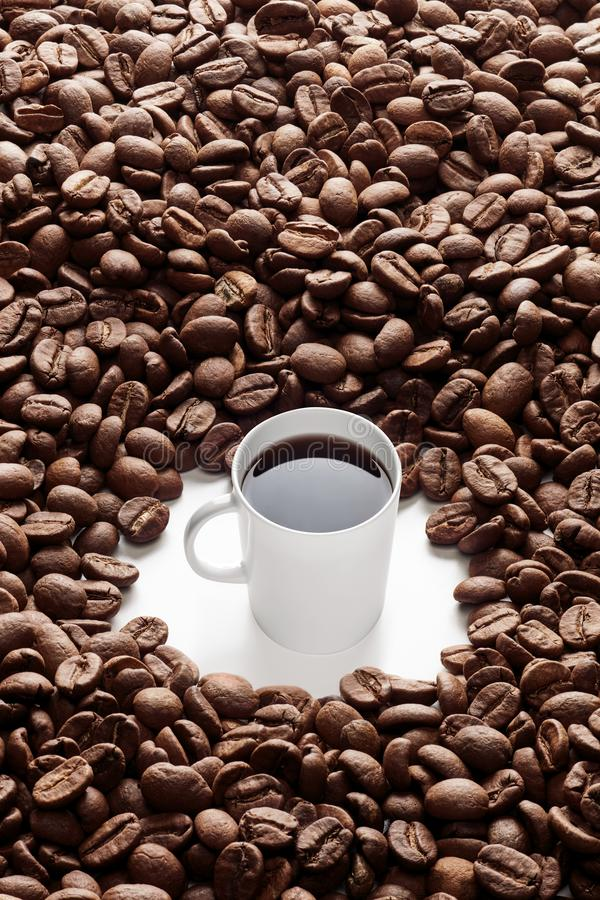 Heap of coffee beans and a mug. White coffee cup surrounded by gigantic roasted coffee beans. Top view stock photo