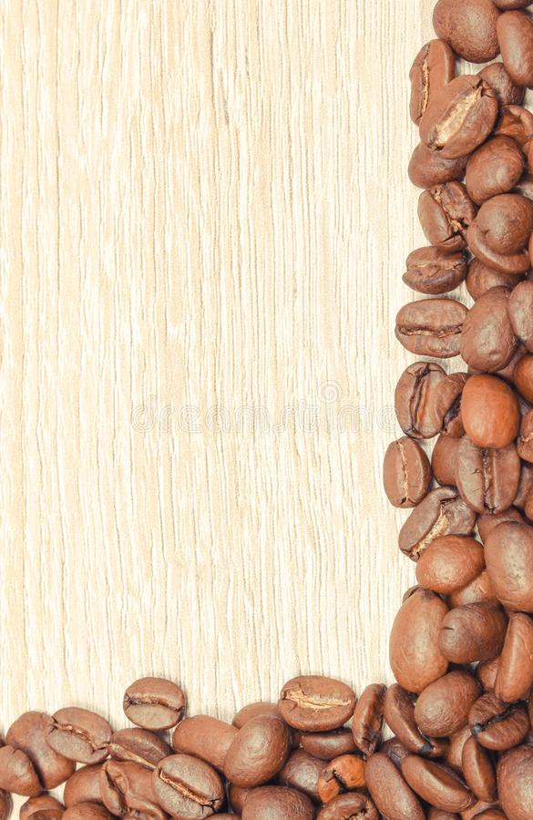 Heap of coffee grains on wooden board. Place for text royalty free stock photography