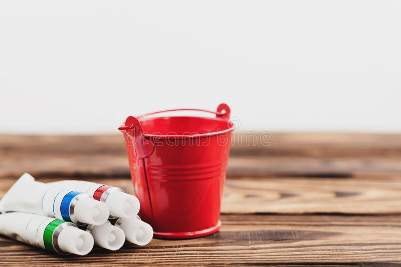 Heap of colorful acrylic paints in closed containers and red empty metal bucket stock photography