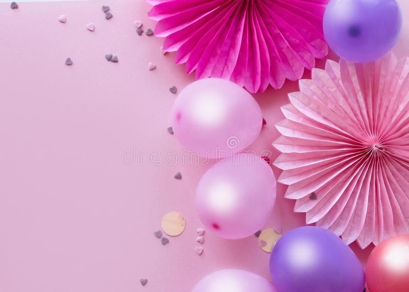 Heap of colorful balloons, confetti and paper flowers on pink table top view. Birthday party backgroundÑŽ stock images