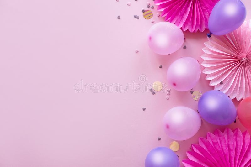Heap of colorful balloons, confetti and paper flowers on pink table top view. Birthday party background. Festive greeting card. stock photos