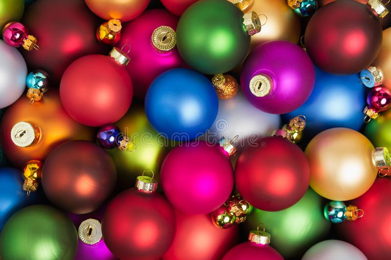 A heap of colorful christmas baubles lying on the floor royalty free stock photo