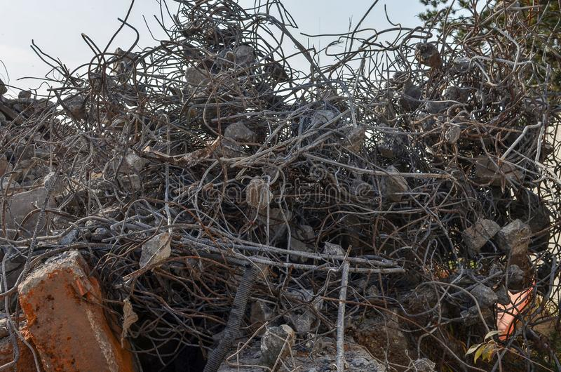 Heap of construction debris: Armature, iron round rods, pieces of broken concrete, curved metal rods. The remnants of broken stock photography