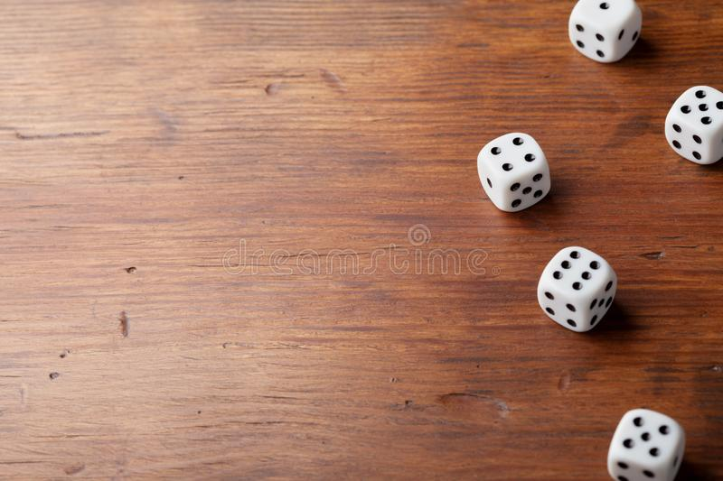 Heap of dice on rustic wooden table. Gambling devices. Game of chance concept. Copy space for text. royalty free stock photo