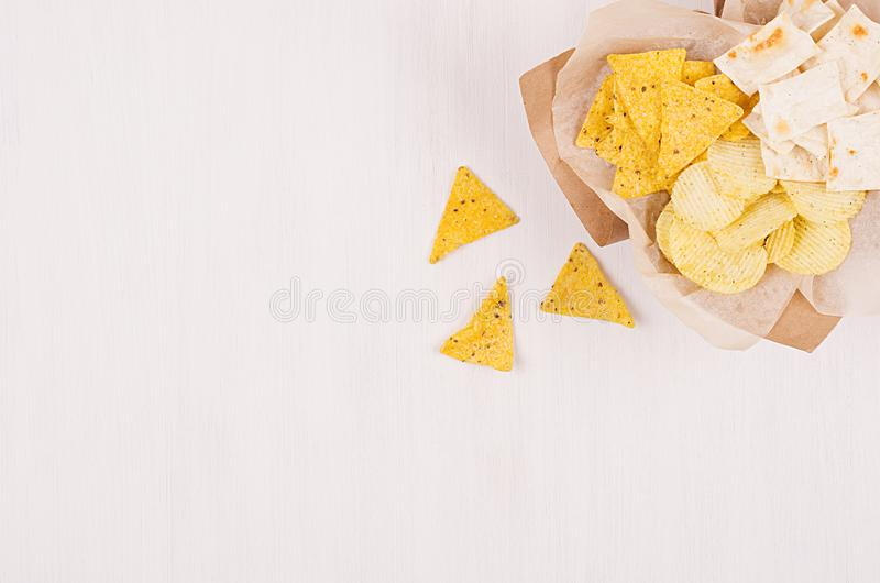 Heap different crispy golden snacks on craft paper, triangles nachos on soft white wood background, with copy space. Summer fresh fast food background stock photo