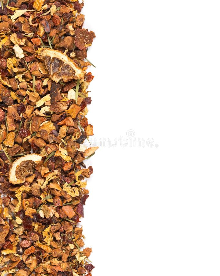 Heap of dried fruit tea infusion with oranges and strawberries mixed with tea leaves and assorted herbs border texture flat lay royalty free stock photo