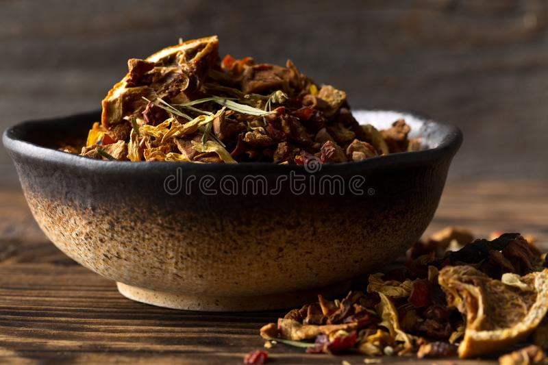 Heap of dried fruit tea infusion with oranges and strawberries mixed with tea leaves and assorted herbs in bowl on wooden table royalty free stock image