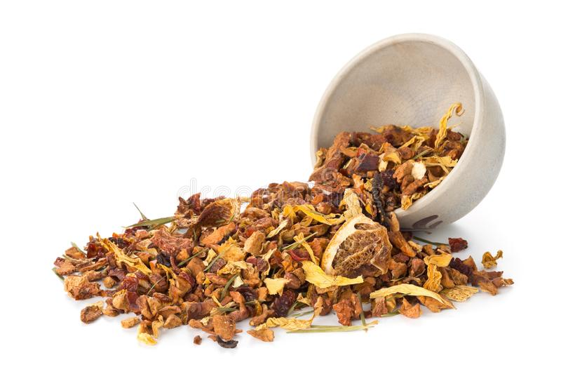 Heap of dried fruit tea infusion with oranges and strawberries mixed with tea leaves and herbs in tea bowl over white background stock image