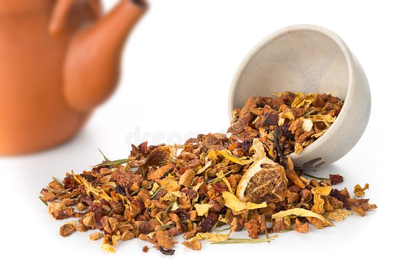 Heap of dried fruit tea infusion with oranges and strawberries mixed with tea leaves and herbs in tea bowl over white background stock photography