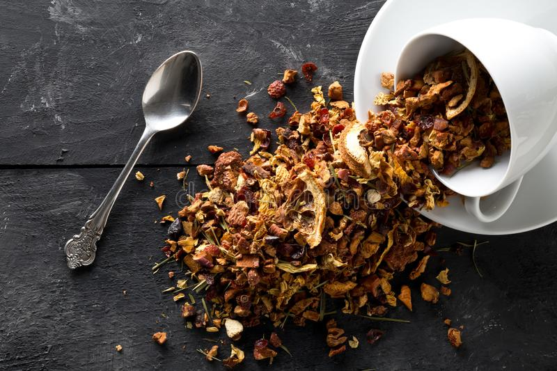 Heap of dried fruit tea infusion with oranges and strawberries mixed with tea leaves and assorted herbs in tea cup and spoon on stock image