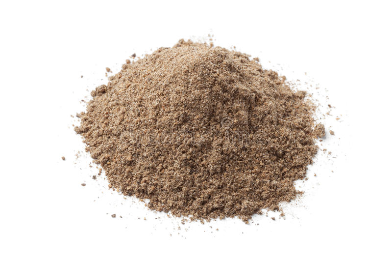 Heap of dried Nutmeg powder. On white background stock photos