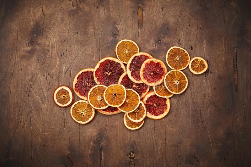 Heap of dried orange rings on dark wooden background stock photos