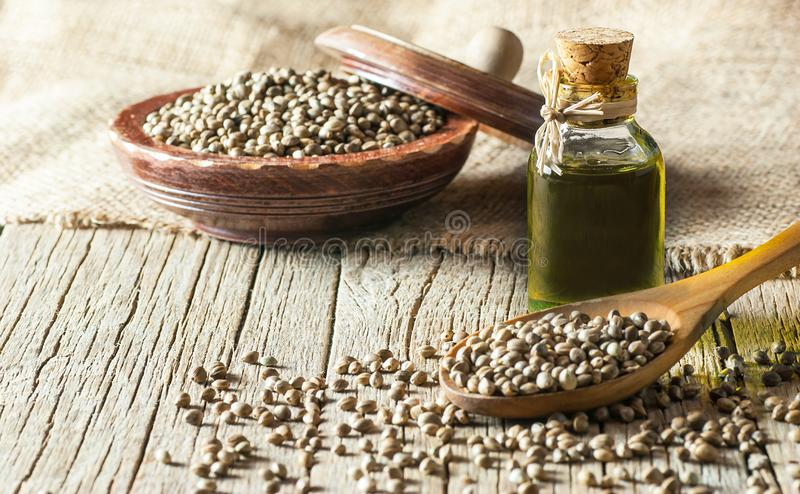Heap of dried organic hemp seeds or cannabis plant seeds in spoon and bowl with glass of hemp seed oil royalty free stock image