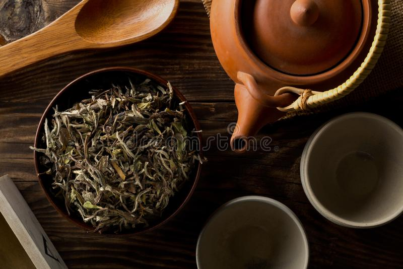 Heap of dried, raw white tea leaves in wooden bowl with teapot and cups on wooden table flat lay top view from above royalty free stock photo