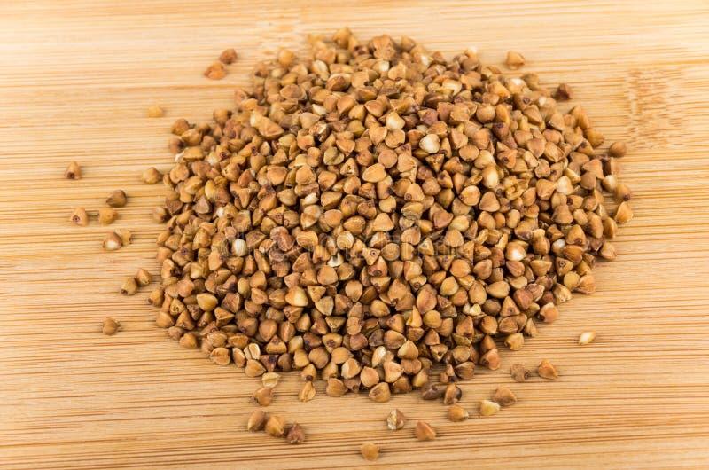 Heap of dry buckwheat on wooden board. Heap of dry buckwheat on wooden bamboo board stock photo