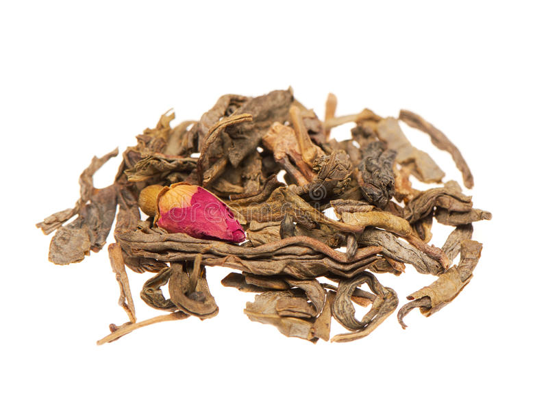 Heap of dry green tea leaves with rose bud royalty free stock photos