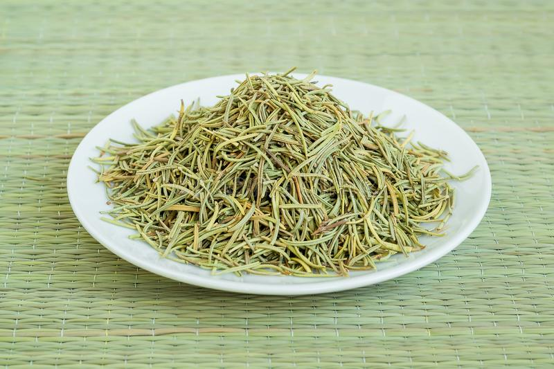 A heap of dry rosemary on a white saucer on a green table mat made of natural plant fibers. Natural food spices and seasonings royalty free stock image