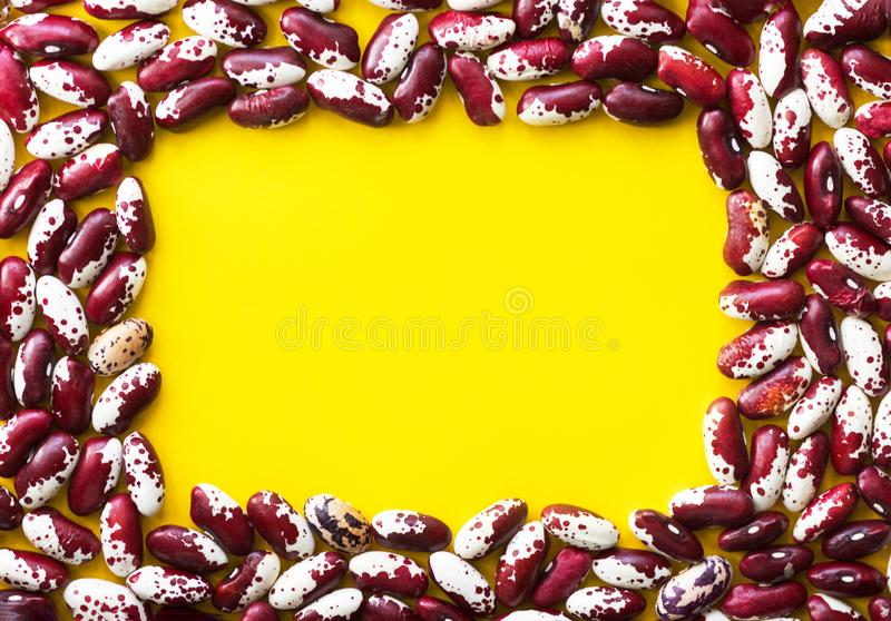 Heap of dry uncooked red and white speckled beans arranged in frame on bright yellow background. Creative food poster. Heart health plant based meatless diet royalty free stock images