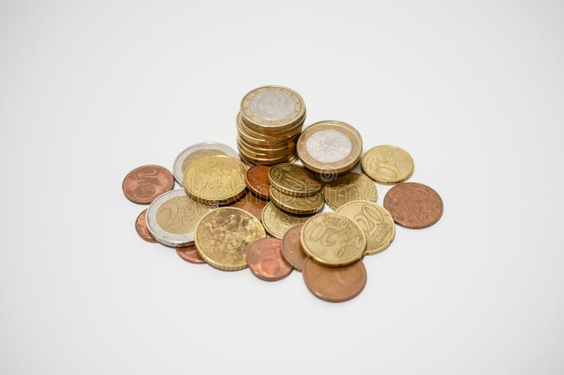Pile of Euro and cents coins of various denominations on a white desk, shallow depth of field stock photos
