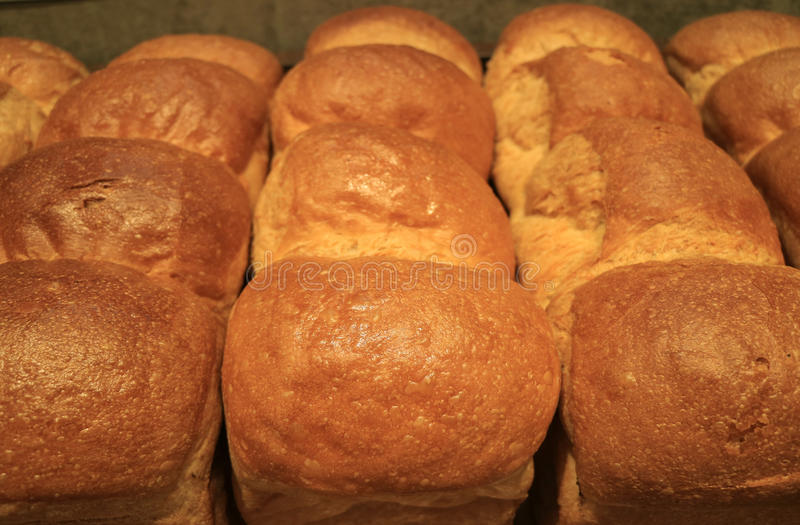 Heap of fluffy fresh baked bread loaves, closed up for background. Texture stock images