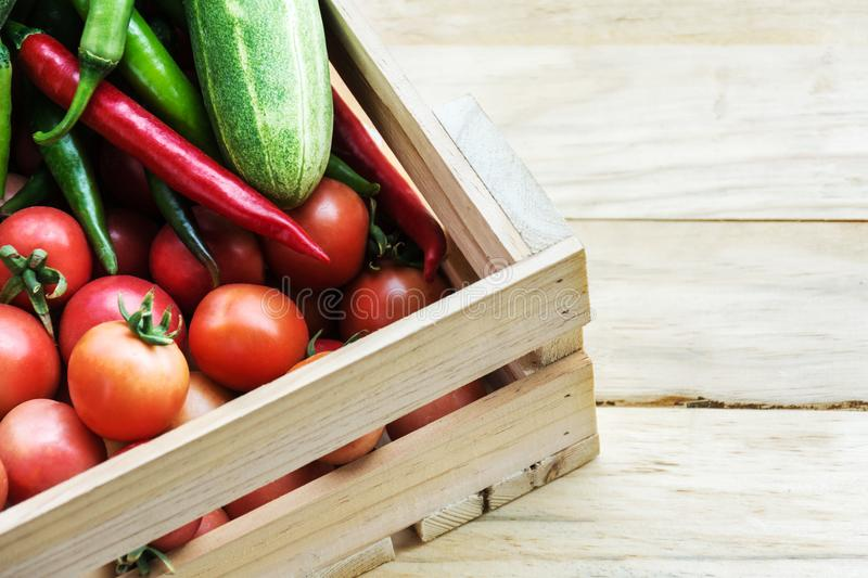Heap of fresh fruits and vegetables in wooden box on wooden back royalty free stock image