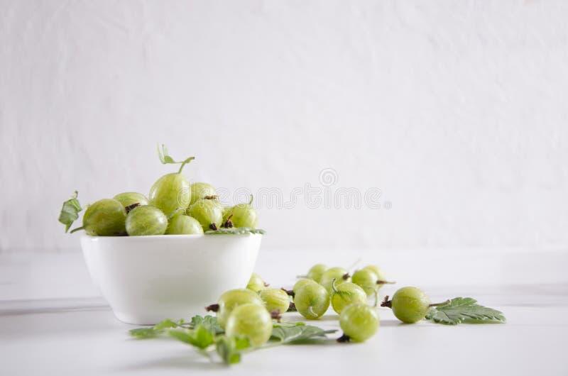 Bowl full of ripe fresh gooseberries on the white table against white background stock photography