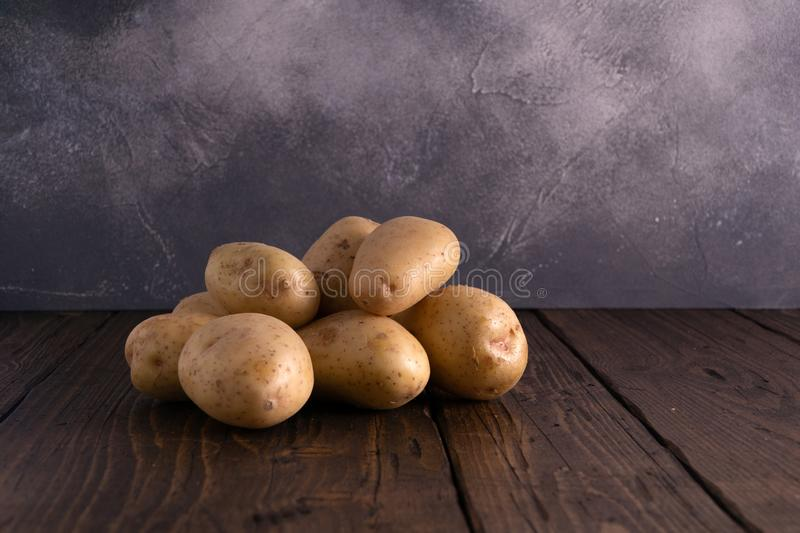 Heap of fresh potatoes on rustic wooden surface and slate textured background. Organic food, carbs, tubers. stock photo