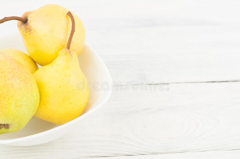 Heap of fresh ripe yellow whole pears in white ceramic bowl royalty free stock photo