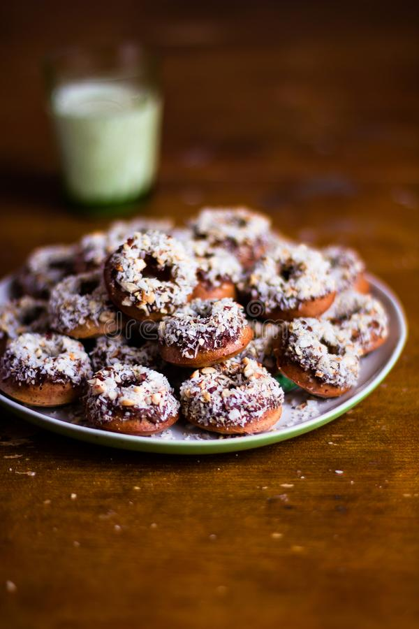 Heap of freshly baked homemade donuts with chocolate cream and coconut on a plate on a wooden table, selective focus. Easter food. stock images