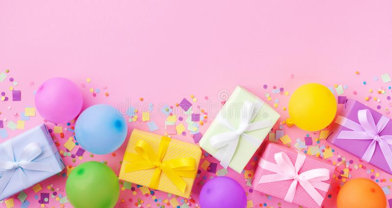 Heap of gift or present boxes, colorful balloons and confetti on pink pastel table top view. Birthday party background. Banner. Format stock image