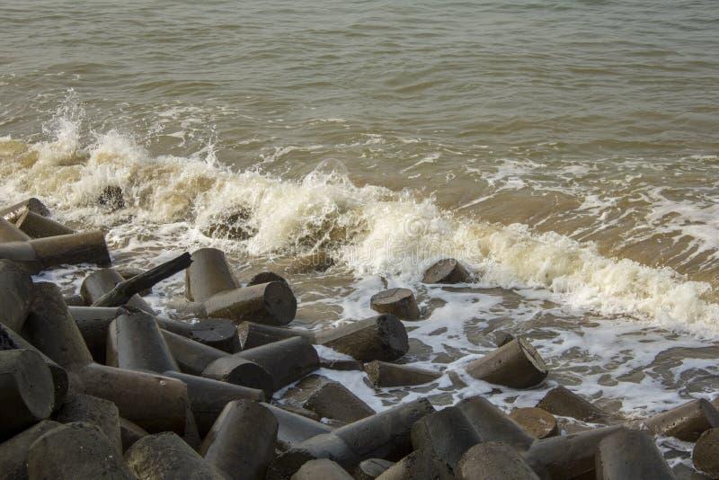 Heap of gray concrete tetrapods, tsunami barrier, in sea waves. A heap of gray concrete tetrapods, tsunami barrier, in sea waves royalty free stock images