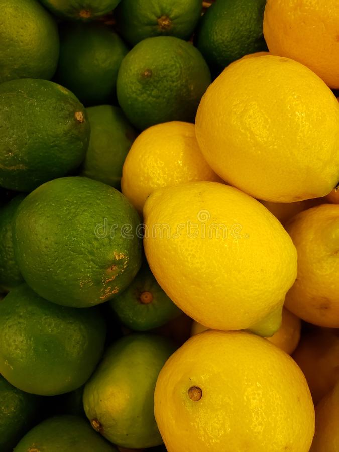 Heap of green and yellow lemon fruit in a market, background and texture. Heap green yellow lemon fruit market background texture citrus  sour sweet ingredient royalty free stock photo