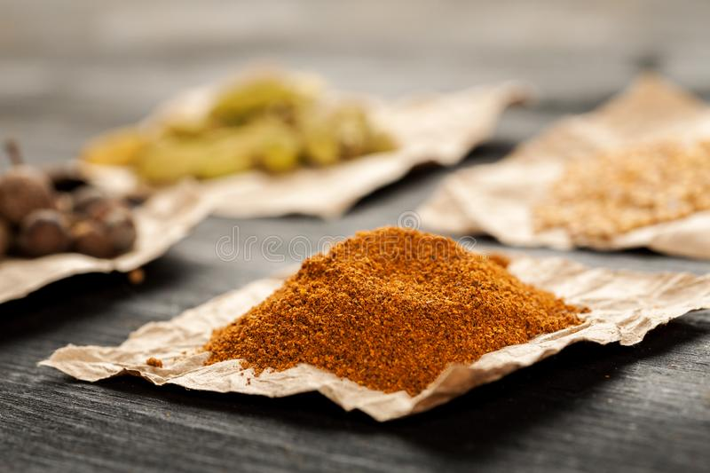Heap of ground red pepper on a piece of craft paper among other spices stock photography