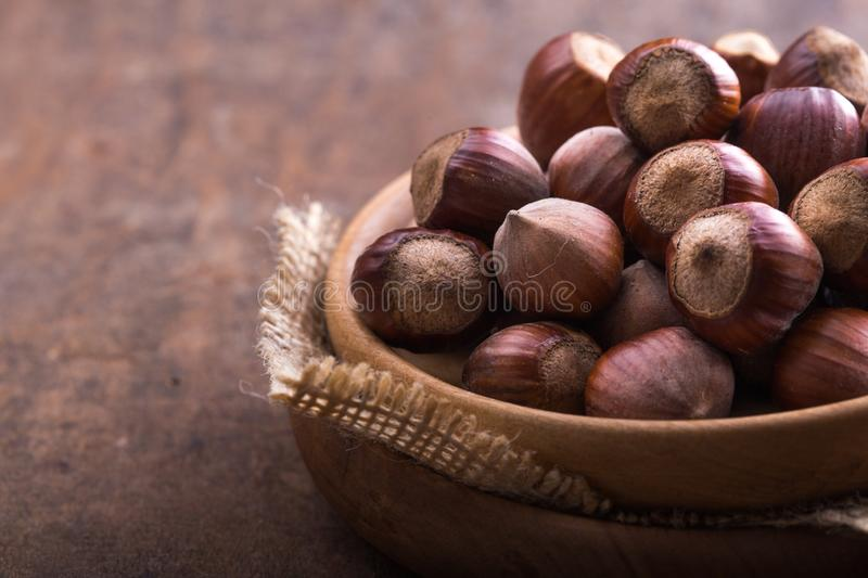 Heap Hazel and nuts with broken shell on an old wooden table. Copy space for text. ZHeap Hazel and nuts with broken shell on an old wooden table. Copy space for stock image
