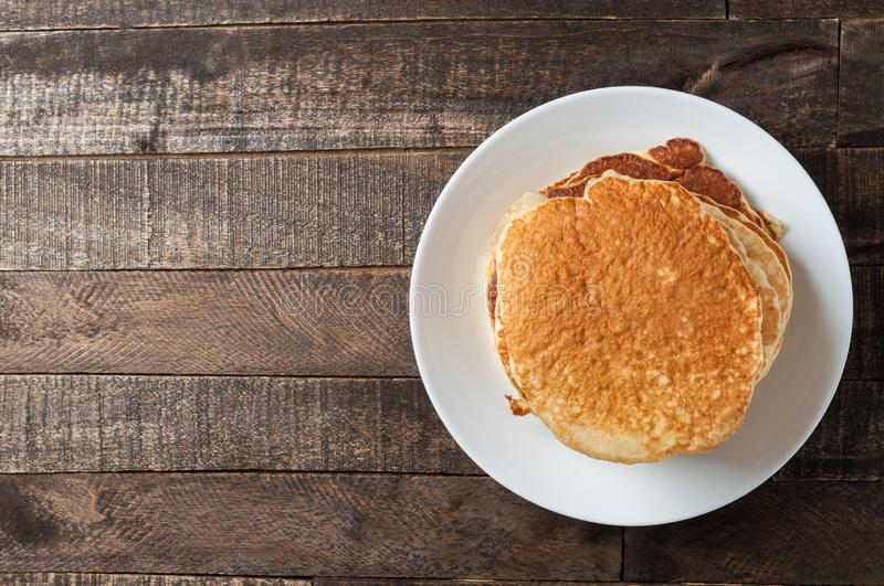 Heap of homemade pancakes without cream lies on round white ceramic plate and old rustic wooden table. Copy space for text. Top view stock photos