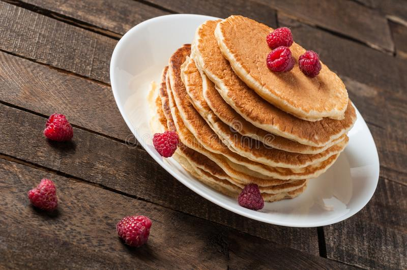 Heap of homemade pancakes with fresh raspberry lies on round white ceramic plate and rustic wooden table stock images