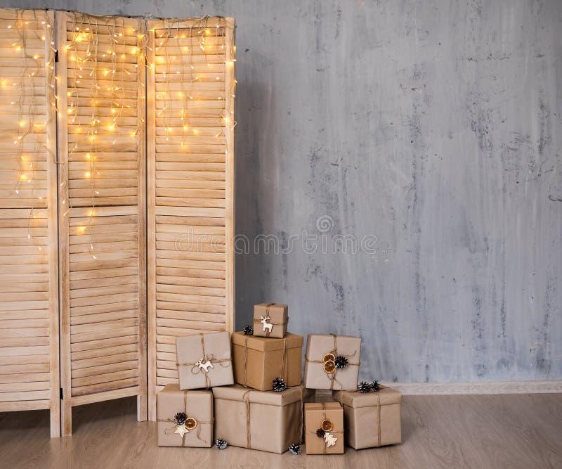 Heap of kerstcadeaus and folding screen with light - kopieer ruimte over betonnen grijze muur stock foto's