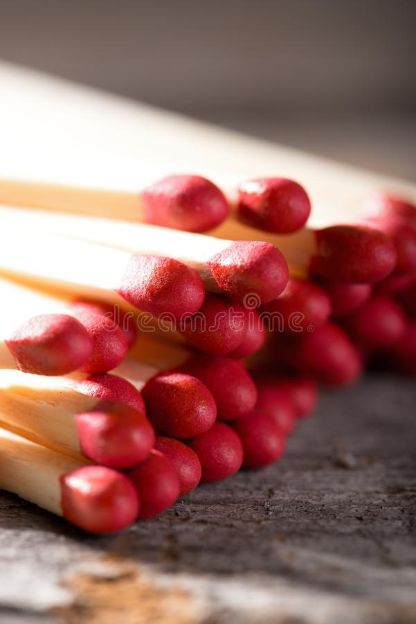 Heap of matchsticks with red heads on wooden board stock image