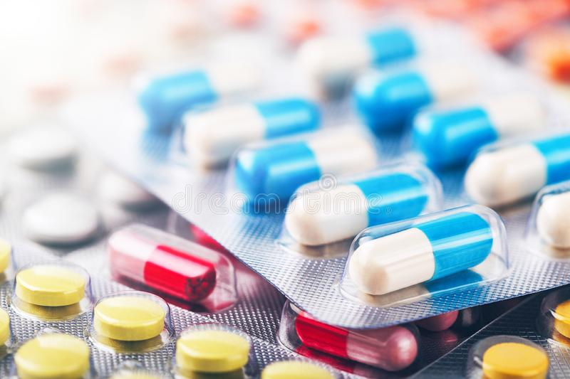 Heap of medical pills in white, blue and other colors. Pills in plastic package. Concept of healthcare and medicine. Heap of medical pills in white, blue and stock photography