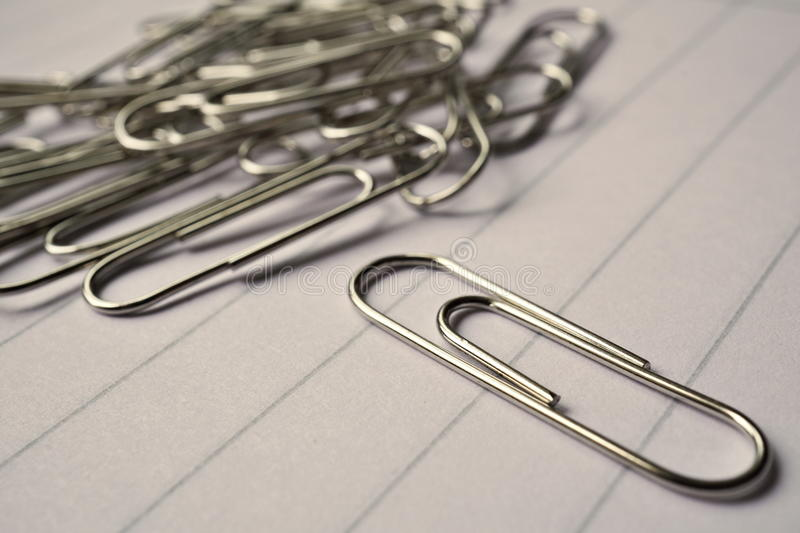 Heap of metal paper clips on white lined paper notepad as a symbol of typical office environment royalty free stock image