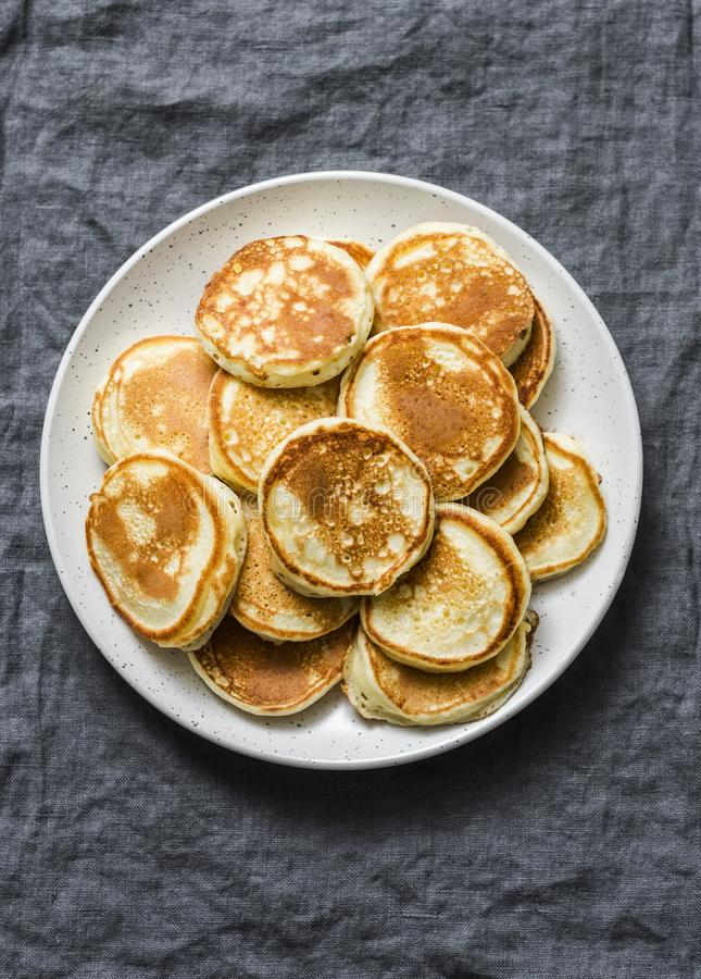 Heap of mini pancakes on a gray background. Delicious breakfast, brunch, dessert royalty free stock images