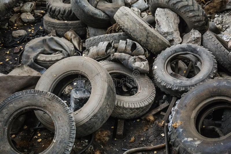 Heap of old car junk tires, used truck rubbish wheels, industrial garbage. Close-up stock photo