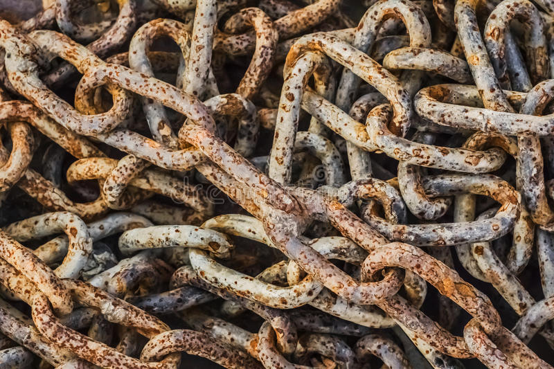 Heap Of Old Rusty Chain Links. Very old, obsolete, weathered, badly corroded, heap of rusty chain links, covered with layers of decomposed metal crust and scales stock image