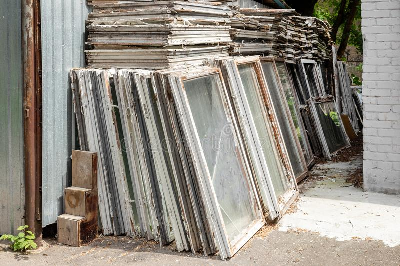 Heap of old wooden window frames with glass outdoors. Broken materials after window energy saving technology upgrade.  stock photography