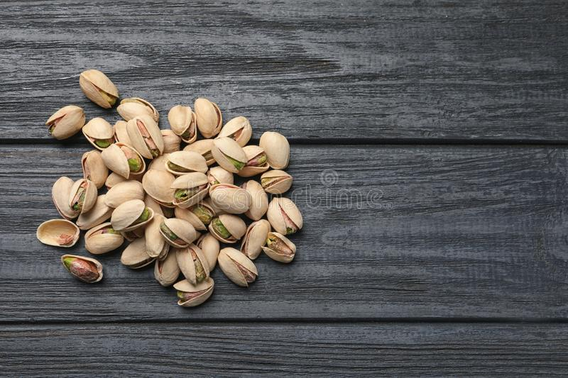 Heap of organic pistachio nuts on wooden table, top view. Space for text royalty free stock photography
