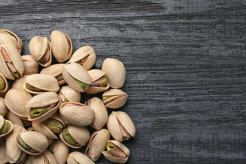 Heap of organic pistachio nuts on wooden table, top view royalty free stock images