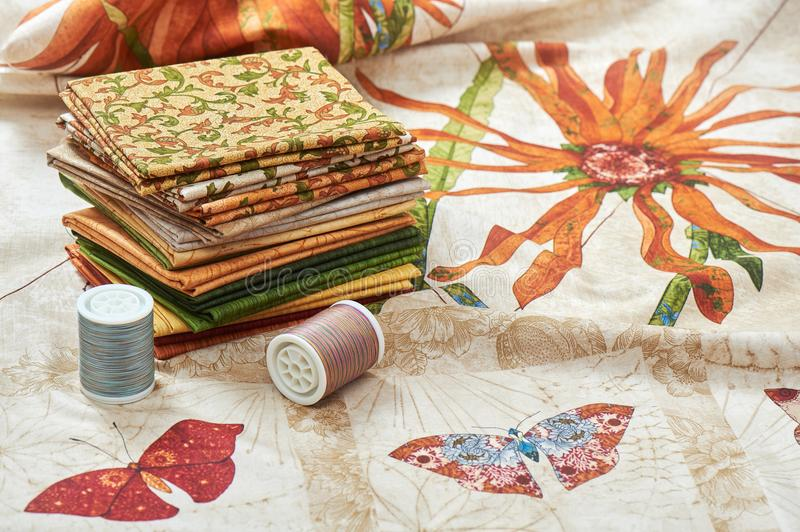 Heap of pieces quilting fabrics lay on cloth with flowers and butterfly images royalty free stock photography