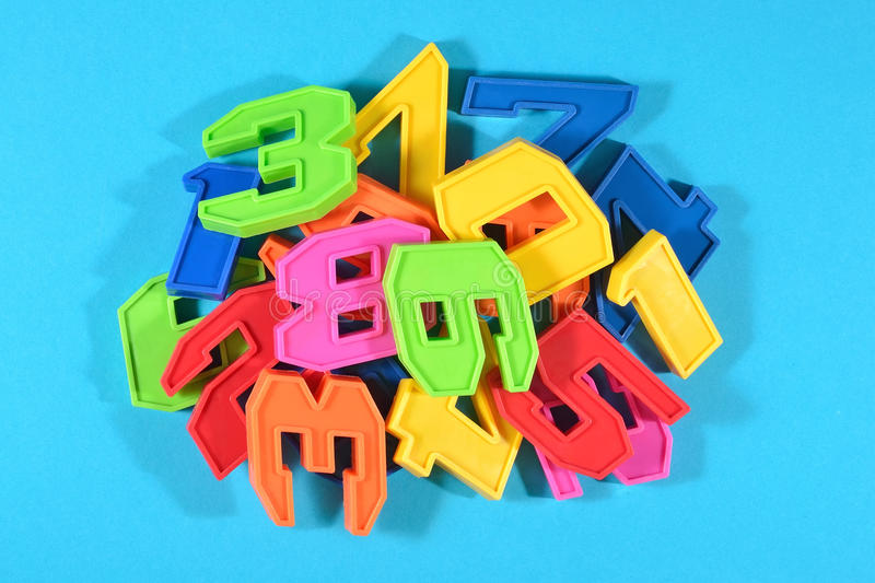 Heap of plastic colored numbers on a blue background. Close up stock photo